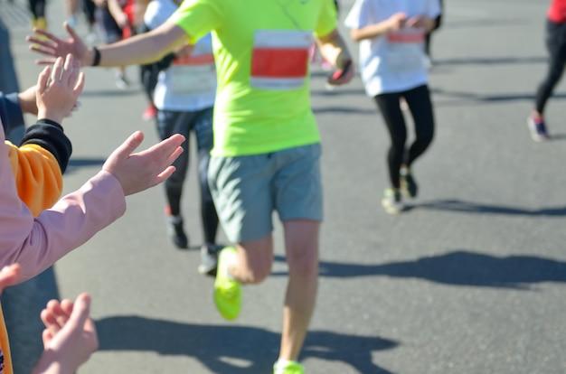 마라톤 달리기 경주, 도로에서 주자를 지원, highfive를주는 어린이 손