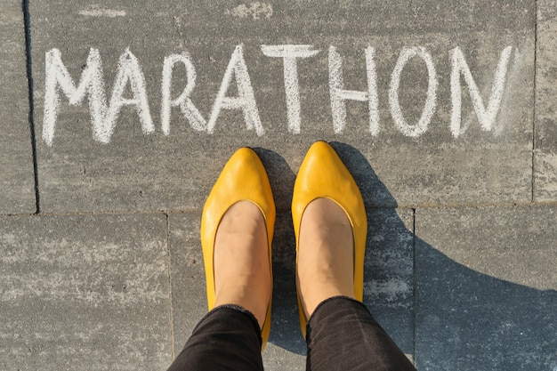Marathon written on gray sidewalk with woman legs, top view