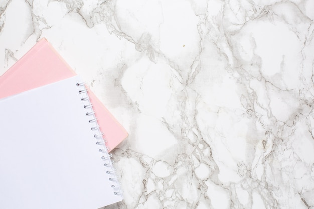 Marble background with white and pink notebook. women business day