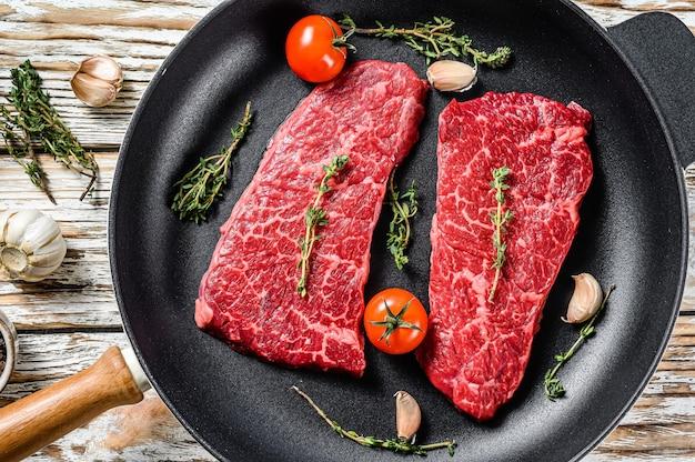 Денверский стейк из мраморной говядины на сковороде с зеленью.
