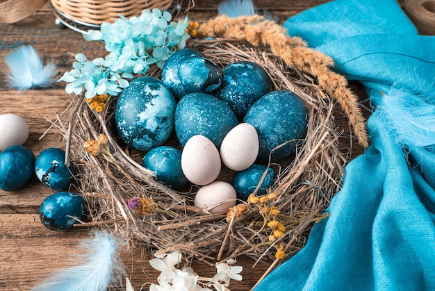 Мраморно-синие пасхальные яйца в плетеном гнезде с перьями и цветами рядом с синей салфеткой и
