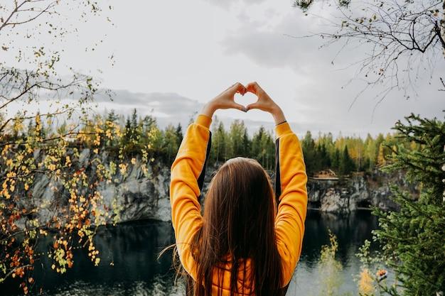 Мраморный каньон в рускеала карелия с девушкой, которая показывает руки сердце над головой