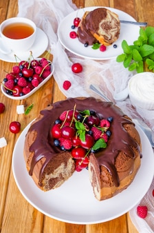 Marble cream cake with chocolate glaze, fresh berries, whipped cream and mint.