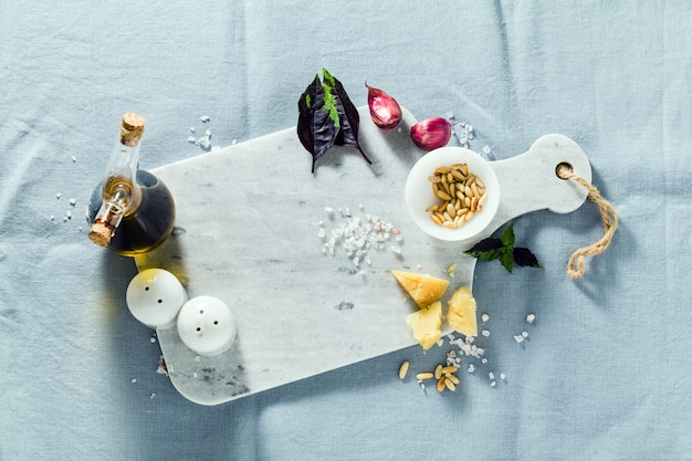 Marble cutting board and spices on a linen blue tablecloth. olive oil, pine nuts and basil. copy space