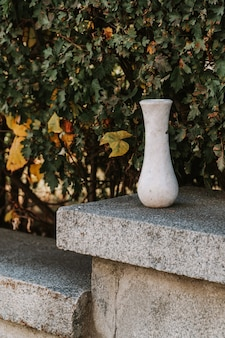 Marble empty vase on green leaves background outdoors