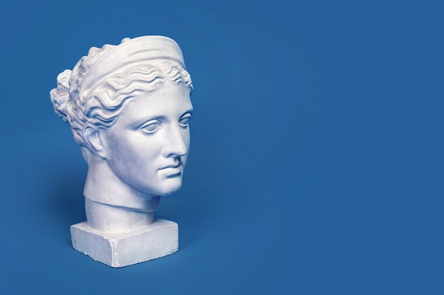 Marble head of young woman, ancient greek goddess bust isolated on blue background. gypsum copy of a statue diana head