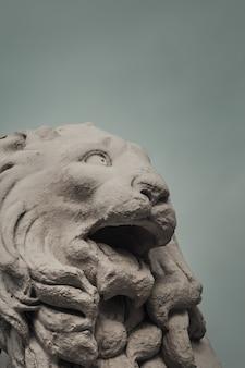 Мраморная голова льва на фоне облачного неба
