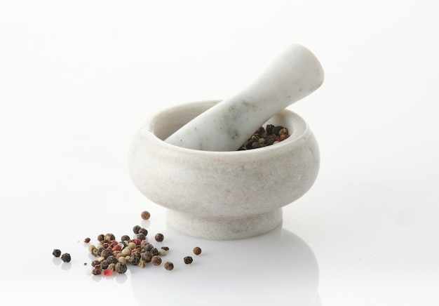 Marble mortar and pestle with spices for grinding isolated on white.