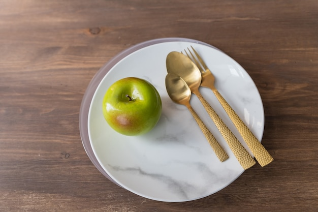 Marble plate, gold knife,fork and spoon on wooden background.dishes and cutlery, plate with spoons and fork.art decor.dinner, romantic love food and love cooking concept. green apple.