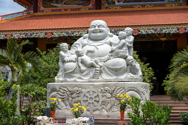 Marble sculpture of the happy buddha with children in a buddhist temple in the city of danang