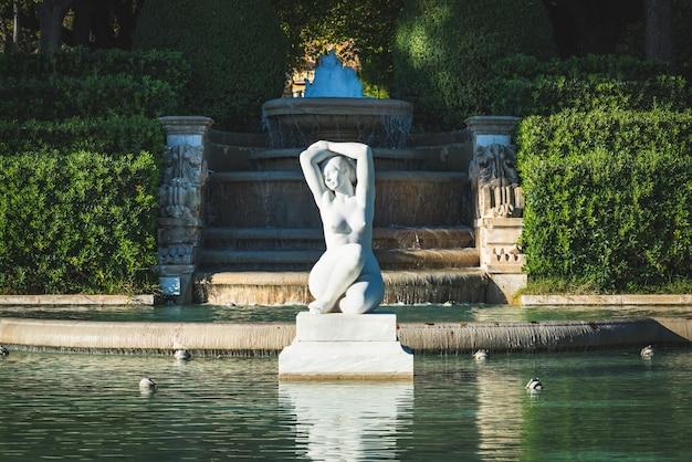 Мраморная скульптура женщины в садовом пруду
