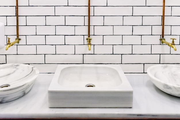 Marble sink in a public restroom with retro golden water tap with copper pipes on wall