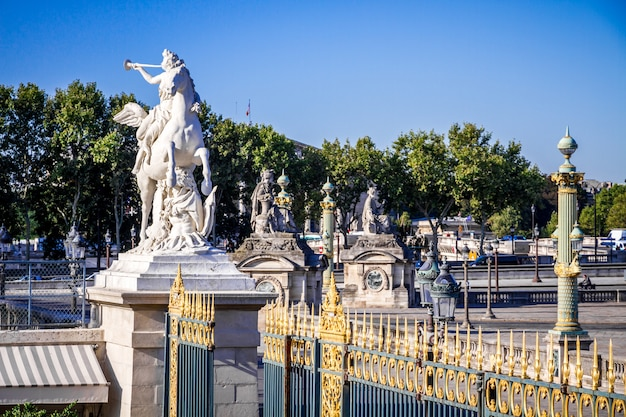 Marble statue and the tuileries garden entrance gate, paris
