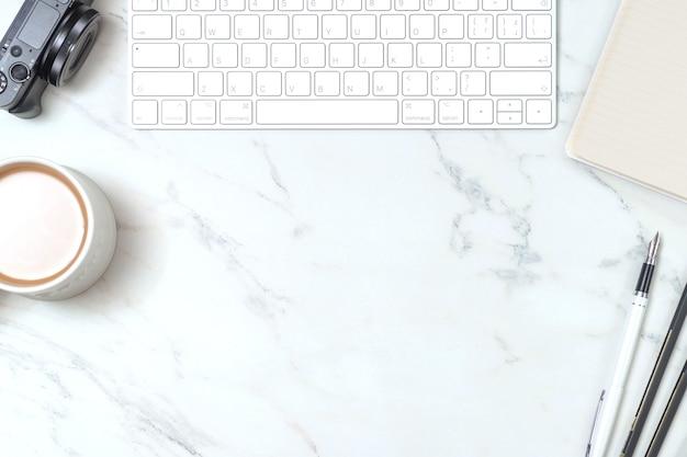 키보드, 펜 태블릿, 커피 및 카메라가있는 대리석 책상