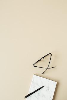 Блокнот, ручка, очки в мраморном стиле на пастельно-бежевой поверхности
