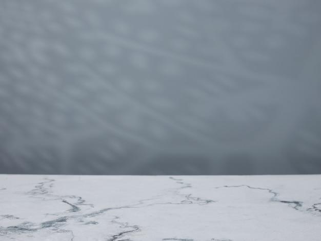 Мраморный стол на фоне бетонной стены с естественными тенями