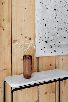 Marble table by an art piece on a wooden wall