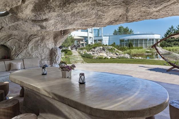 조경된 정원이 있는 시골 부동산의 안뜰 아래에 설치된 바위 동굴의 대리석 테이블