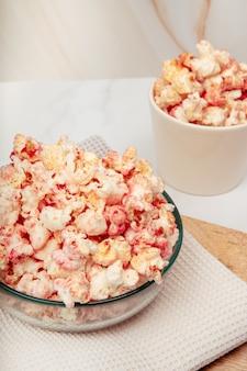 유리 그릇과 도자기와 핑크 팝콘이있는 대리석 테이블