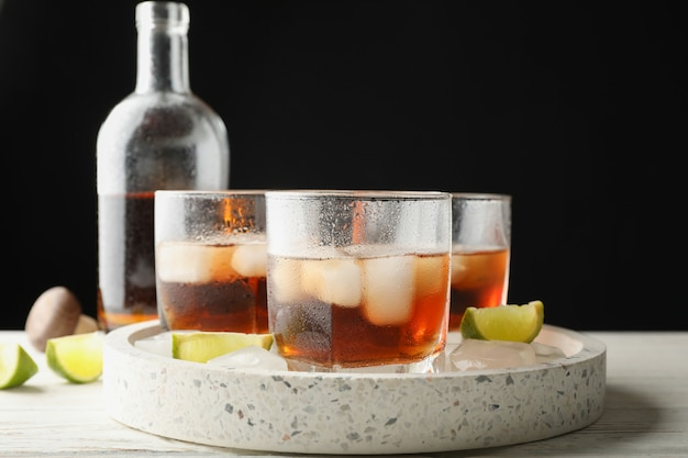 Marble tray with glasses of whiskey and limes on white background, close up