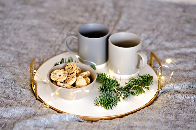 On a marble tray with a gold rim, there are two gray cups of tea and a chocolate gingerbread cookie. a treat for santa claus. christmas tree branch with garlands decorate the new year card. copy space