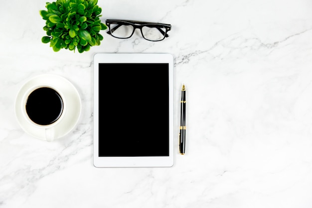 Marble white desk with coffee,glasses,tablet,pen business concept.