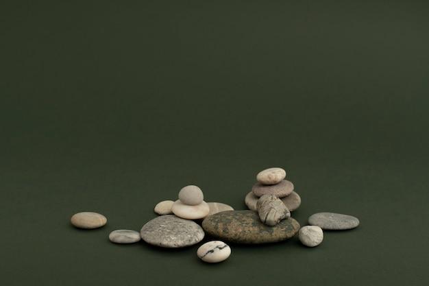 Pietre di marmo zen impilate su sfondo verde in concetto di salute e benessere