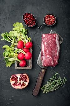 Ингредиенты карпаччо из мраморной говядины, редис, филе говядины, гранатовый набор, на черном каменном фоне, плоская планировка, вид сверху, с местом для текста