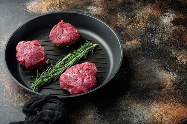 Мясо из мраморной говядины black angus steak set, вырезка из вырезки филе миньон, на чугунной сковороде, на старом темном деревенском фоне, с местом для текста