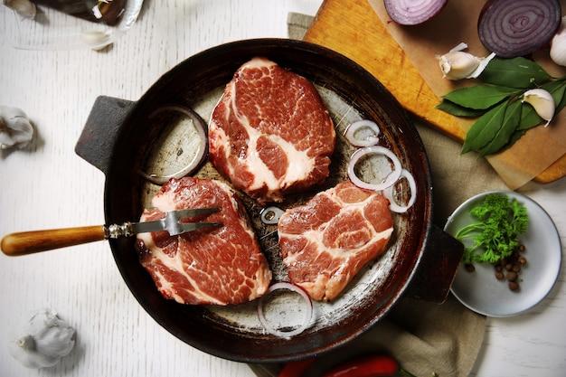 鍋に霜降り肉のステーキ、木製の色にスパイス