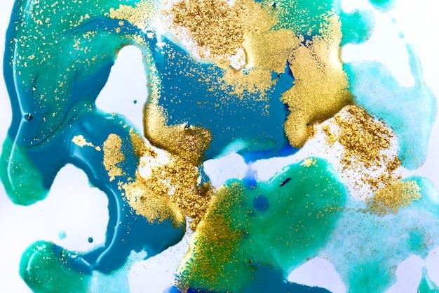Мраморные синие и золотые жидкие чернила на фоне белой бумаги.