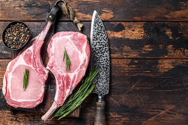 마블링된 생 돼지갈비 고기 스테이크 또는 토마호크. 어두운 나무 배경입니다. 평면도. 공간을 복사합니다.