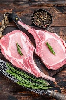 마블링된 생 돼지갈비 고기 스테이크 또는 토마호크. 어두운 나무 배경입니다. 평면도.