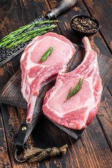Мраморные сырые свиные отбивные, мясной бифштекс или томагавк.