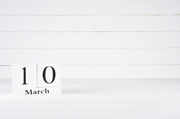 March 10th, day 10 of month, birthday, anniversary, wooden block calendar on white wooden background with copy space for text.