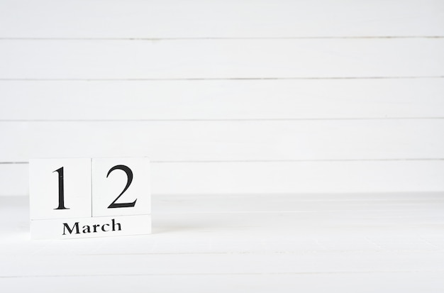 March 12th, day 12 of month, birthday, anniversary, wooden block calendar on white wooden background with copy space for text.
