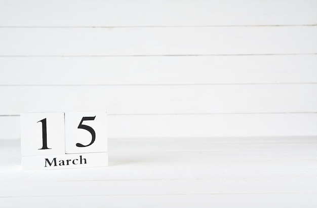 March 15th, day 15 of month, birthday, anniversary, wooden block calendar on white wooden background with copy space for text.