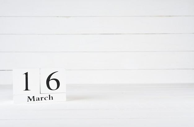 March 16th, day 16 of month, birthday, anniversary, wooden block calendar on white wooden background with copy space for text.