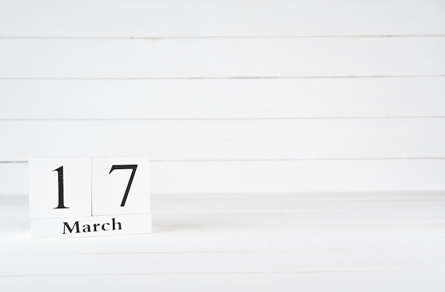 March 17th, day 17 of month, birthday, anniversary, wooden block calendar on white wooden background with copy space for text.