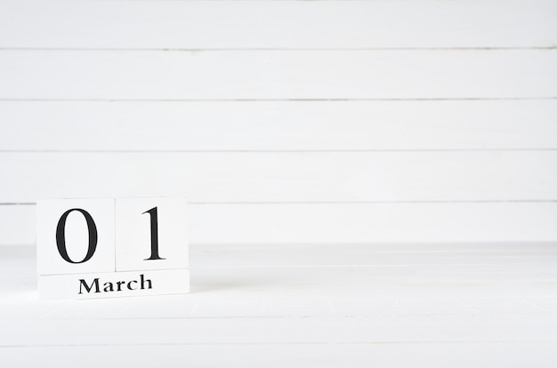 March 1st, day 1 of month, birthday, anniversary, wooden block calendar on white wooden background with copy space for text.