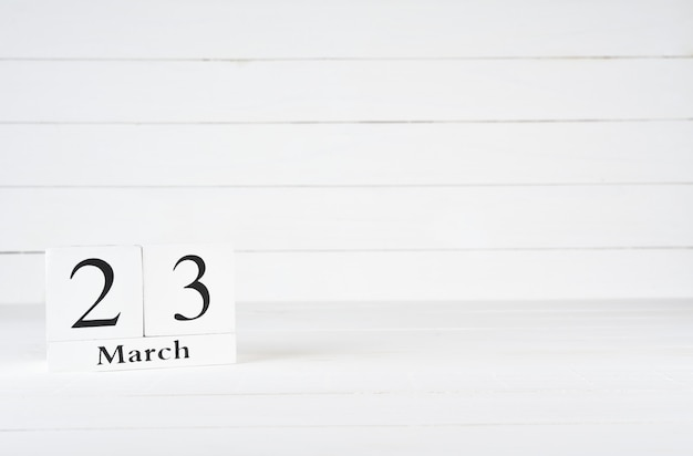 March 23rd, day 23 of month, birthday, anniversary, wooden block calendar on white wooden background with copy space for text.