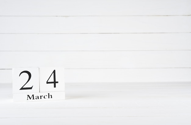 March 24th, day 24 of month, birthday, anniversary, wooden block calendar on white wooden background with copy space for text.