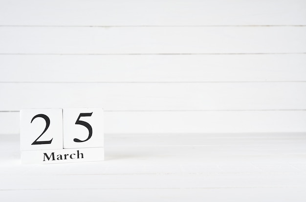 March 25th, day 25 of month, birthday, anniversary, wooden block calendar on white wooden background with copy space for text.