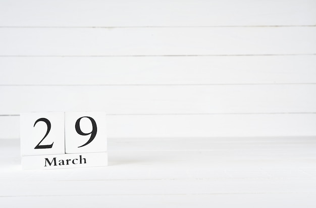 March 29th, day 29 of month, birthday, anniversary, wooden block calendar on white wooden background with copy space for text.