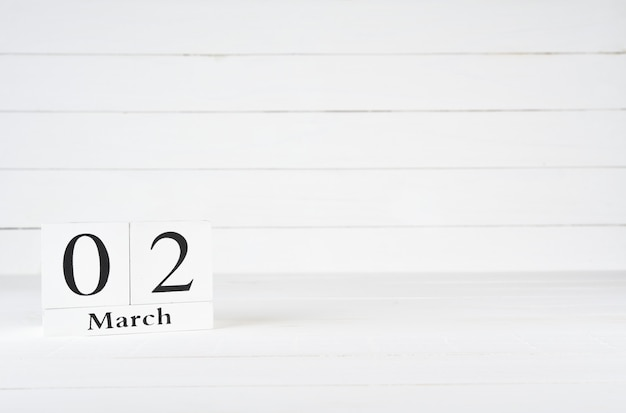 March 2nd, day 2 of month, birthday, anniversary, wooden block calendar on white wooden background with copy space for text.