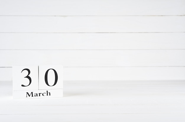 March 30th, day 30 of month, birthday, anniversary, wooden block calendar on white wooden background with copy space for text.