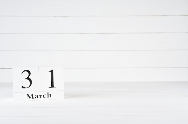 March 31st, day 31 of month, birthday, anniversary, wooden block calendar on white wooden background with copy space for text.