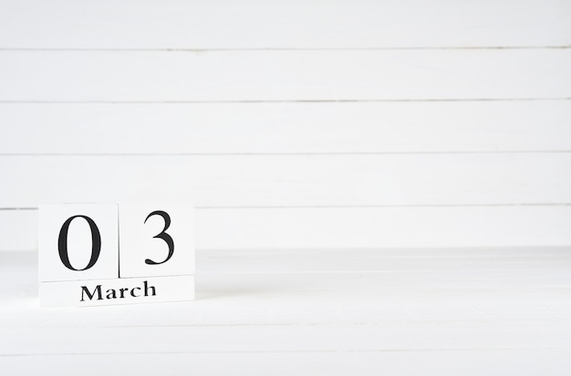 March 3rd, day 3 of month, birthday, anniversary, wooden block calendar on white wooden background with copy space for text.