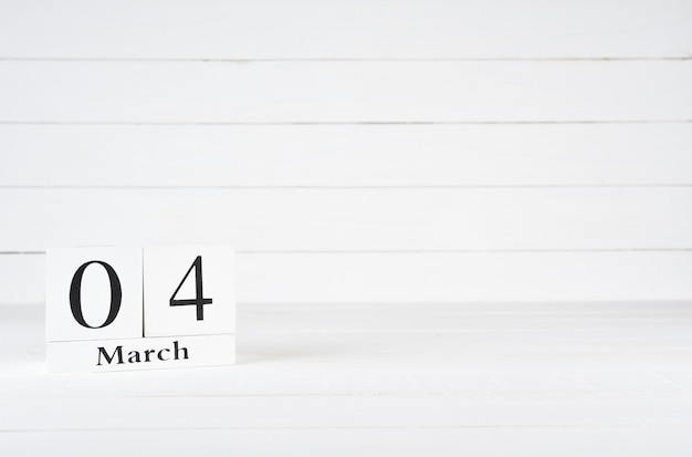 March 4th, day 4 of month, birthday, anniversary, wooden block calendar on white wooden background with copy space for text.
