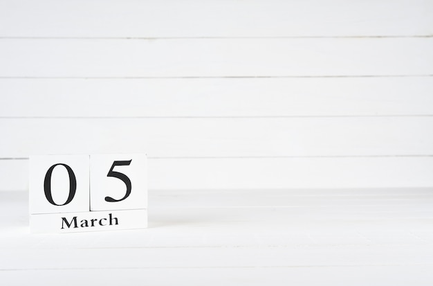 March 5th, day 5 of month, birthday, anniversary, wooden block calendar on white wooden background with copy space for text.